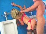 Bloncka v červeném podvazkovém pásu šuká na pánských záchodech - freevideo